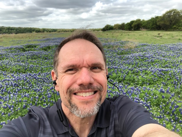 Man in field of bluebonnets